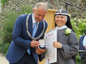 Namens het College van B&W ontvingen wij, uit handen van burgemeester Heijmans...
